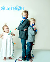 Silent Night Child Portrait- a little girl has her two brothers tied with christmas lights by Jax Custom zphotography